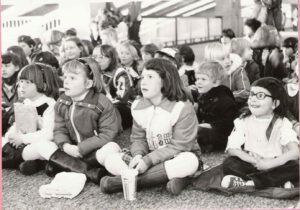 Black and white photo of kid audience. They're very engaged
