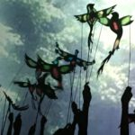 Shadows of hands holding colourful puppets of birds with the backdrop of clouds in the sky